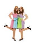 Twee Beierse geklede meisjes die hun voeten opheffen Stock Foto