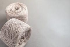 Twee beige ballen van het garen van de dradenwol op grijs document stock afbeelding