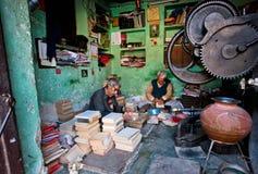 Twee bejaarde arbeiders die oude boeken in een workshop herstellen Royalty-vrije Stock Foto's