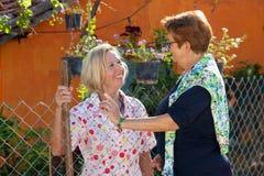 Twee bejaarde dames die in de tuin babbelen Royalty-vrije Stock Foto