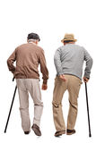 Twee bejaarde mensen die met riet lopen dat op witte backgrou wordt geïsoleerd Stock Foto