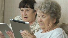 Twee bejaarde zusters die zilveren digitale tabletten houden stock footage