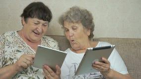 Twee bejaarden die de digitale tabletten houden stock video