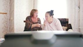 Twee bejaarden die op TV en het becommentariëren letten stock video