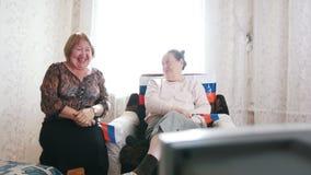Twee bejaarden die op TV letten en Russische vlaggen golven stock videobeelden