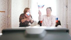 Twee bejaarden die op TV letten en Russische vlaggen golven Gevend elkaar hoogte vijf stock footage
