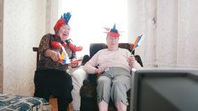 Twee bejaarden die op TV in Russische toebehoren letten en Russische vlaggen golven stock video