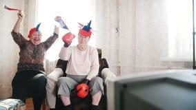 Twee bejaarden die op TV in Russische toebehoren letten en Russische vlaggen in langzame motie golven stock video