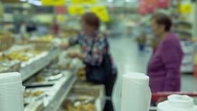 Twee bejaarden in een supermarkt verbeteren stock footage