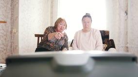 Twee bejaarden gingen zitten om op TV te ontspannen en te letten stock footage