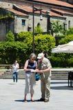 Twee bejaarden raadplegen een kaart Stock Afbeelding