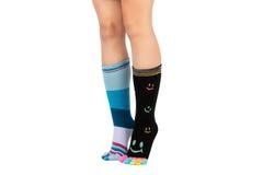 Twee benen in verschillende gelukkige sokken met tenen Stock Foto