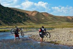 Twee bergfietsers en rivier Stock Afbeelding