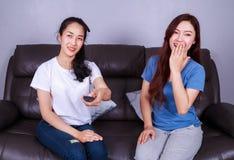 Twee beste vrienden die op TV met ver op bank thuis letten Stock Afbeeldingen