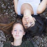 Twee beste vrienden die van het tienermeisje op de rotsen, hoogste mening liggen outdoors stock foto's