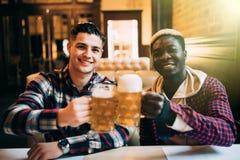 Twee beste vrienden of universiteitspartners die bier hebben bij bar Afro Amerikaanse mens die aan zijn Kaukasische vriend in bar royalty-vrije stock fotografie