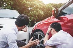 Twee bestuurdersmens die na een het ongevallenbotsing van het autoverkeer debatteren, stock fotografie