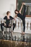 Twee bevallige ballerina's, één die de spleten en één zitting op stoel, op de marmeren vloer doen Schitterende balletdansers stock foto