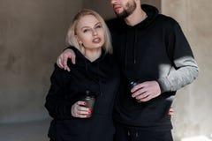 Twee bevinden de jonge modieuze mensenmens zich en een meisje in in zwarte sweatshirts en houden een zwarte kop van koffie in han royalty-vrije stock foto's