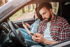 Twee bezige mensen zitten in auto en kijken aan hun telefoons Zij spreken niet met elkaar Zij maakten een einde royalty-vrije stock afbeelding