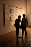 Twee bezoekers die of kunststuk bewonderen bespreken Stock Foto