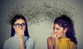 Twee bezorgde vrouwen die elkaar bekijken die met vele gedachten ruilen royalty-vrije stock afbeeldingen
