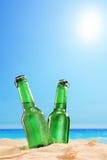 Twee bierflessen op een zandig strand, naast een overzees Stock Foto's