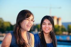Twee biracial jonge en vrouwen die in openlucht glimlachen spreken stock afbeelding