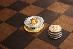 Twee Bitcoins en Amerikaanse centen op een schaakbord stock afbeeldingen