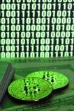 Twee bitcoins ligt op een stapel van dollarrekeningen op de achtergrond van een monitor die een binaire code van heldergroene nul Stock Foto