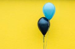 Twee blauwe ballons tegen een heldere gele muur Royalty-vrije Stock Foto's