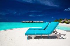 Twee blauwe stoelen op zandig eiland die tropisch overweldigen overzien zijn Stock Afbeelding