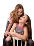 Twee blije tienersmeisjes die op wit worden geïsoleerd Stock Foto