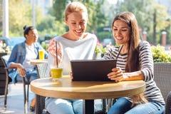 Twee blije vrouwen die op video op tablet in koffie letten Royalty-vrije Stock Afbeeldingen