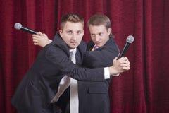 Twee blijspelacteurs met microfoons Stock Foto's