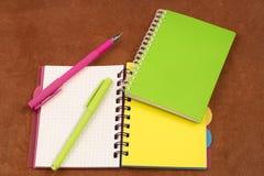 Twee blocnotes en twee pennen op een bruine achtergrond stock afbeeldingen