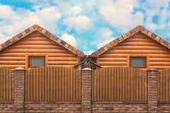 Twee blokhuizen met een bruine omheiningstribune zij aan zij Buurt, een nieuw district royalty-vrije stock foto