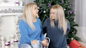 Twee blonde haardames die over iets spreken die op het tapijt dichtbij de Kerstboom situeren stock footage