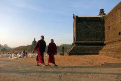 Twee boeddhistische monniken die in rode kledingstukken voor de tempel lopen stock foto's