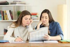 Twee bored studenten die een krant lezen stock foto's