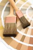 Twee borstels op een gids van het kleurenpalet stock foto's