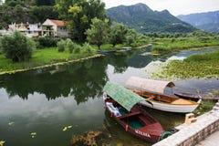 Twee boten bij de pijler op de rivierbank Bergen en struiken op de achtergrond stock afbeelding