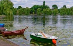 Twee boten op de kust van de vijver, rode en groene boten op het meer Stock Foto's
