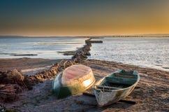 Twee boten van vissers, aan de grond bij zonsondergang dichtbij de lagune en een houten dok stock afbeelding