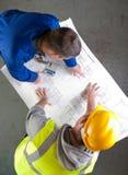 Twee bouwers bespreken bouwblauwdrukken Royalty-vrije Stock Foto's