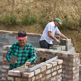 Twee bouwers die muren maken stock foto's