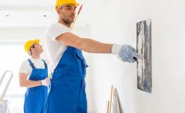 Twee bouwers met het schilderen van hulpmiddelen die ruimte herstellen stock afbeelding