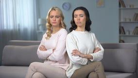 Twee boze vrouwen die in ruziezitting zijn op bank, conflict tussen vrienden stock footage