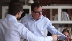Twee boze zakenlieden die hebbend conflictconfrontatie op het werk debatteren stock videobeelden