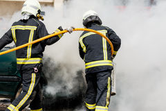 Twee brandbestrijders die een autobrand doven Stock Foto